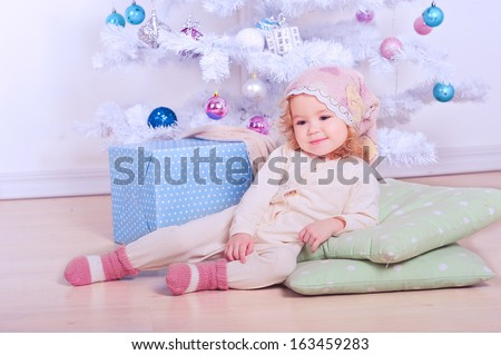 Cute baby girl lying on the floor under christmas tree indoors - stock photo