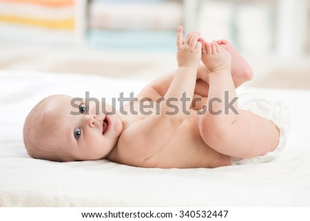 Cute baby girl lying on white sheet and holding her legs - stock photo