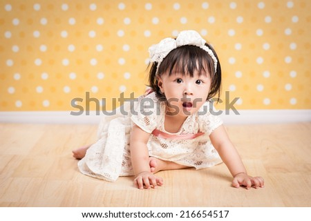 Cute baby girl makes a funny upset face crawling isolated on a yellow background. - stock photo