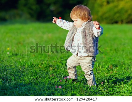 cute baby girl making first steps, colorful outdoors - stock photo