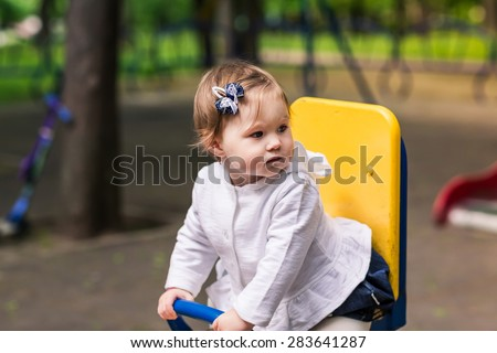 Cute baby girl on a seesaw swing at the playground - stock photo