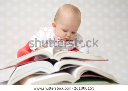Cute baby girl reading behind a pile of books - stock photo