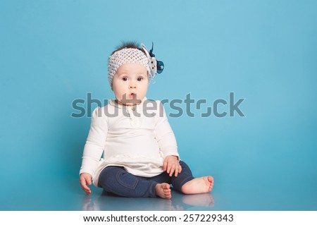 Cute baby girl sitting in room over blue. Wearing trendy dress. Looking surprised at camera. Childhood. - stock photo