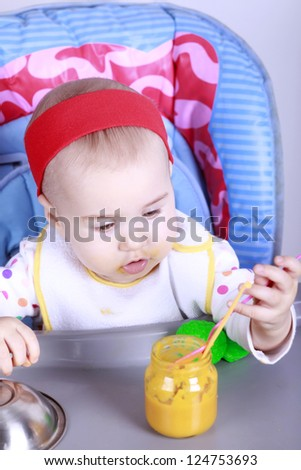 Cute baby girl sitting on high chair and learn to eat - stock photo