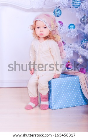 Cute baby girl sitting under christmas tree in room - stock photo