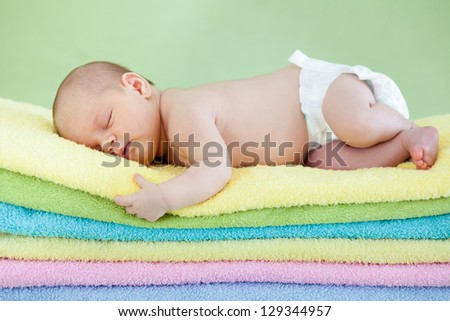 cute baby girl  sleeping on colourful towels - stock photo