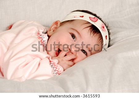 cute baby girl sucking on fingers - stock photo