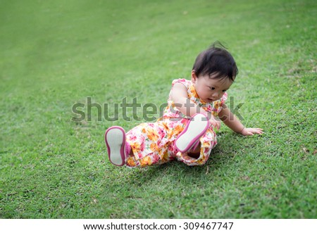 Cute baby girl try to walk and fall down in the park - stock photo