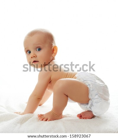 Cute baby girl trying to get on her feet to make first steps - stock photo