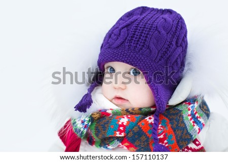 Cute baby girl wearing a warm winter hat and a colorful scarf on a walk in a snowy park - stock photo