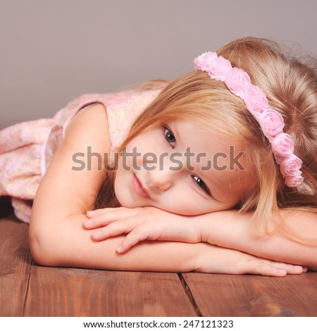 Cute baby girl wearing pink headband and trendy dress lying on wooden floor in room. Resting. Childhood. - stock photo