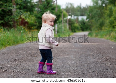 Cute baby girl with blonde hair running outdoors. Little girl 1-2 year old. - stock photo