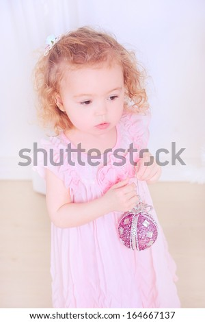 Cute baby girl with christmas ball indoors - stock photo