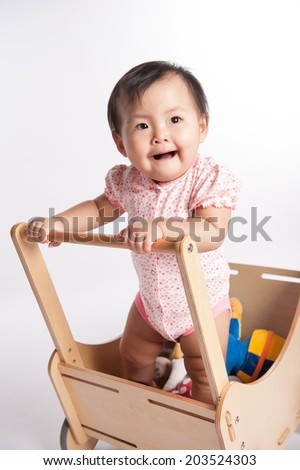 Cute baby girl with funny face and standing up in crib - stock photo
