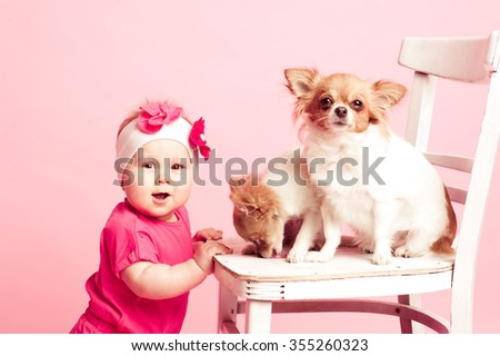 Cute baby girl 1 year old playing with pets in room. Looking at camera. - stock photo