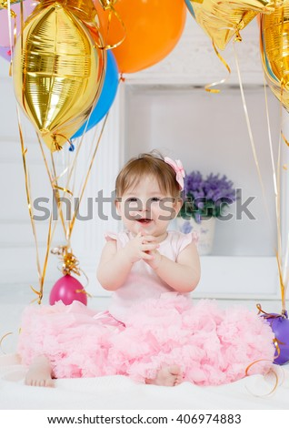 Cute baby girl 1-2 year old sitting on floor with pink balloons in room over white. Isolated. Birthday party. Celebration. Happy birthday baby, Little girl with group ball. Play room. - stock photo