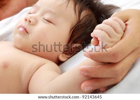 Cute baby holding mom's hand - stock photo