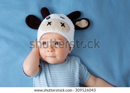 cute baby in a cow hat on blue blanket - stock photo