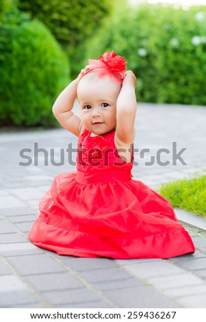 cute baby in a red park nature plays - stock photo