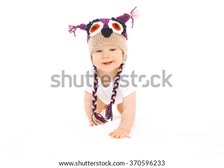 Cute baby in knitted hat crawls on white background - stock photo