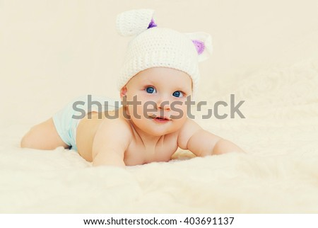 Cute baby in knitted hat with rabbit ears crawls on bed home - stock photo