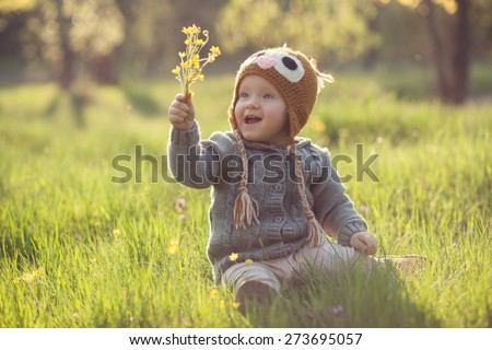 Cute baby in knitwears playing at the garden - stock photo