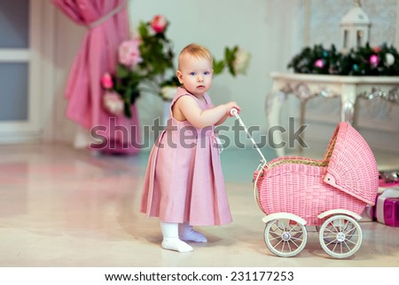 cute baby in pink dress rolls the stroller on the background of the Christmas tree - stock photo