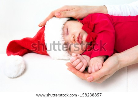 Cute baby in Santa hat sleeping in mother??s hands - stock photo