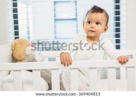 Cute baby in the crib looking around - stock photo