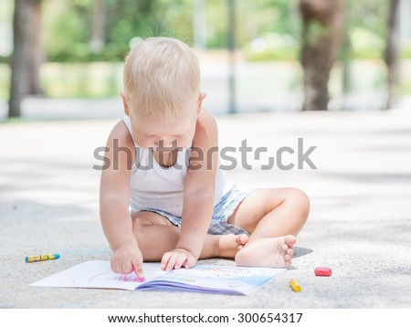 Cute baby is painting outdoor - stock photo