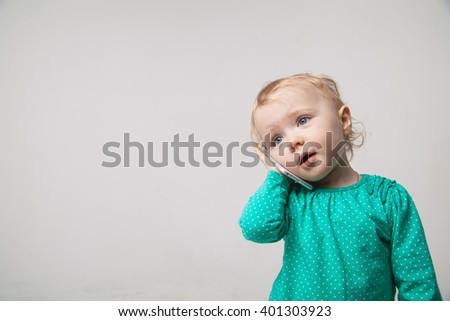 Cute  baby is talking on cell phone,  - stock photo