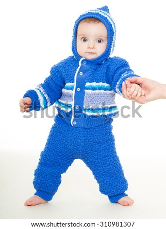 Cute baby learning to walk. Beautiful happy baby in a blue dress . One, isolated on white. - stock photo