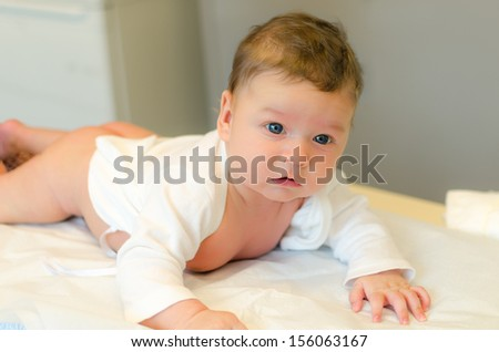 Cute baby lies on his tummy in a clinic and looks at camera - stock photo