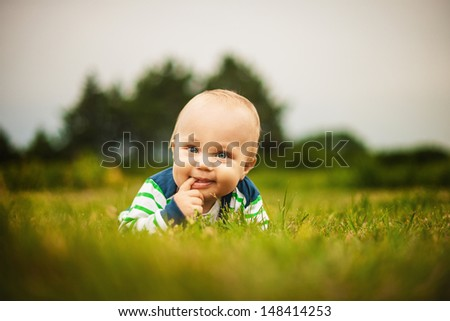 Cute baby looking at camera and smiling while lying on the grass outdoors in sunlight - stock photo