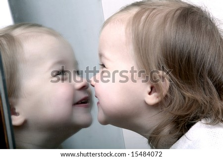 Cute baby looking into mirror, laughing - stock photo