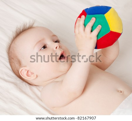 Cute baby lying and holding a ball - stock photo