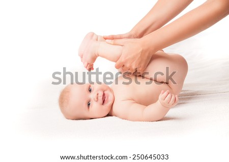 Cute baby lying on white blanket legs pulled to face. Isolated over white background. - stock photo