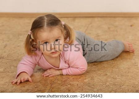 Cute baby lying on wooden floor. - stock photo