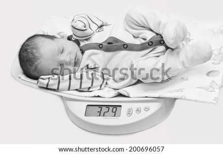 cute baby on the scales on a white background ( black and white ) - stock photo