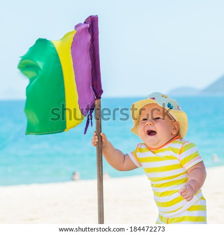 Cute baby on the tropical beach with flag - stock photo