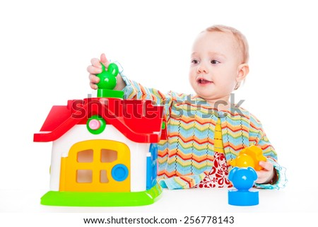 Cute baby play with toy house on white backdrop - stock photo