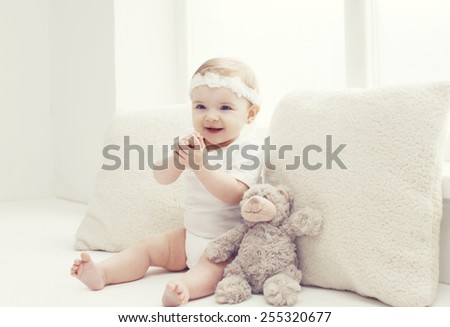Cute baby playing at home in white room near window - stock photo