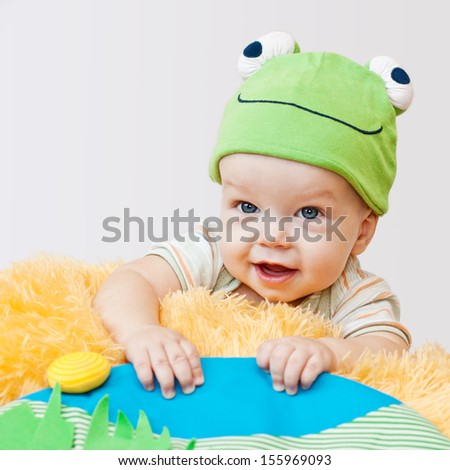 cute baby playing in the hat frog lying on his stomach on a white background - stock photo