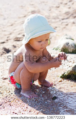 cute baby playing on the beach with water - stock photo