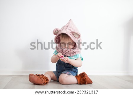 Cute baby playing. Snood, jeans, moccs - stock photo