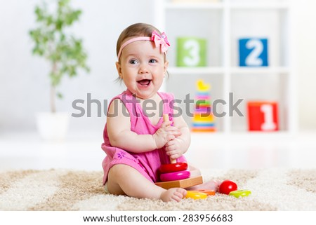 cute baby playing with colorful toy pyramid at home - stock photo