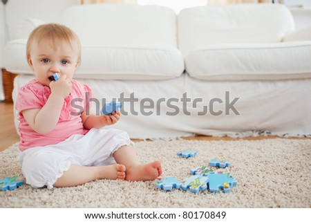 Cute baby playing with puzzle pieces while sitting on a carpet in the living room - stock photo