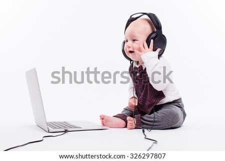 Cute baby sitting in front of a laptop wearing headphones on a white background smiling and listening to music, picture with depth of field - stock photo