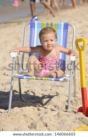 cute baby sitting on a beach chair - stock photo