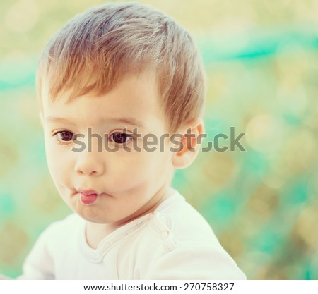Cute baby sitting outdoors - stock photo